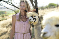Portrait of blond woman with leashed alpaca - ECPF00499