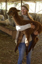 Portrait of smiling mature woman carrying young alpaca in her arms - ECPF00502
