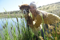 Portrait of smiling blond woman head to head with alpaca in nature - ECPF00514