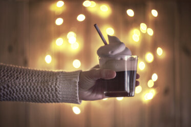 Hand holding coffee with cream, bokeh lights on the background - EPF00558