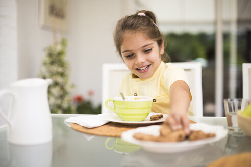 Happy little girl taking a cookie during breakfast at home - ABZF02226