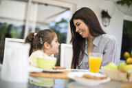 Happy mother and daughter having breakfast at home - ABZF02229