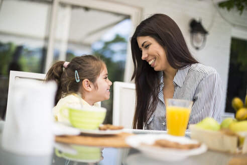 Mother and daughter smiling and having fun during breakfast in Madrid, Spain. - ABZF02229