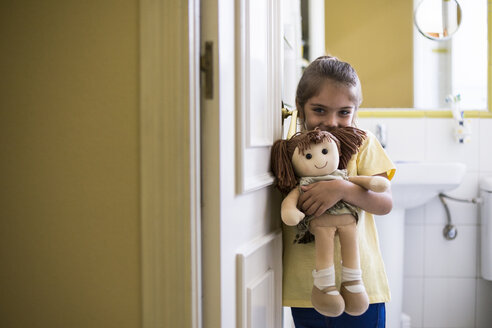 Portrait of smiling little girl standing in doorframe at home holding a doll - ABZF02232