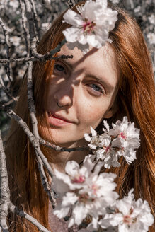 Portrait of redheaded woman behind twigs of blossoming tree - AFVF02387