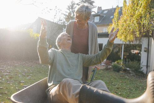 Happy senior couple having fun with wheelbarrow in garden - KNSF05504