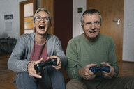 Excited senior couple playing video game at home - KNSF05507