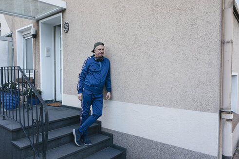 Sportive senior man in tracksuit leaning against house wall - KNSF05510