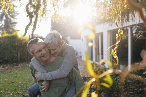 Happy senior man carrying wife piggyback in garden - KNSF05513