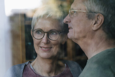 Confident senior couple looking out of window - KNSF05522