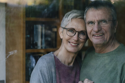 Portrait of happy senior couple behind windowpane - KNSF05528