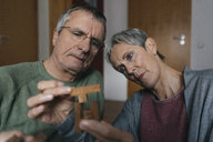Senior couple playing dexterity game at home - KNSF05543