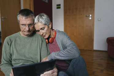 Senior couple sitting on the floor at home looking at tablet - KNSF05546