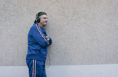 Sportive senior man in tracksuit leaning against house wall - KNSF05549