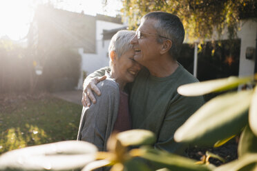 Happy affectionate senior couple hugging in garden - KNSF05564