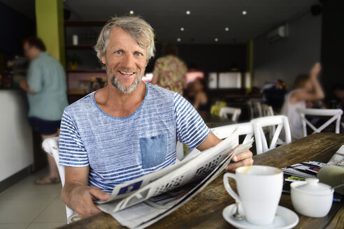 Portrait of smiling mature man sitting in a coffee shop reading newspaper - ECPF00515
