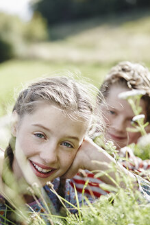 Portrait of smiling girl lying on a meadow with little brother at the background - RORF01742