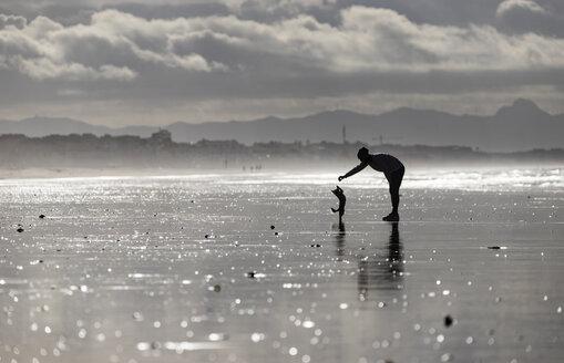 Spanien, Andalusien, Tarifa, Frau mit Hund, Strand - KBF00495