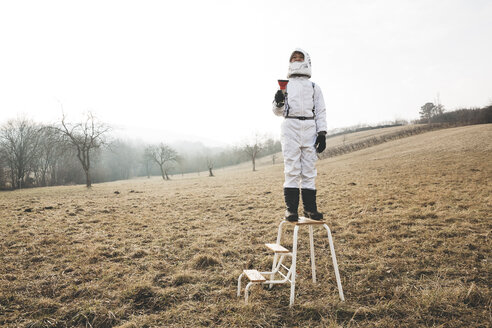 six year old cool boy wearing white space suit ist posing outdoor in a meadow, sometimes with virtual reality glasses - HMEF00202