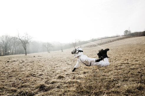 Boy wearing white space suit is posing outdoor on a meadow with virtual reality glasses - HMEF00205
