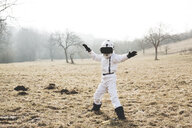 Boy wearing white space suit is posing outdoor on a meadow with virtual reality glasses - HMEF00208