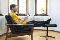 Casual man  in yellow shirt sitting in Lounge Chair in stylish apartment looking on tablet - SBOF01721