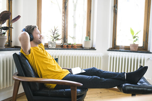 Rrelaxed man in yellow shirt with headphones sitting in Lounge Chair in stylish apartment - SBOF01724