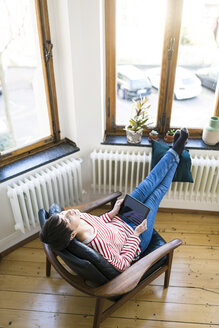 Short-haired woman relaxing in lounge chair holding tablet in stylish apartment - SBOF01733