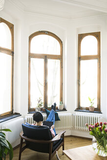 Short-haired woman with headphones and tablet relaxing in lounge chair holding tablet in stylish apartment - SBOF01736