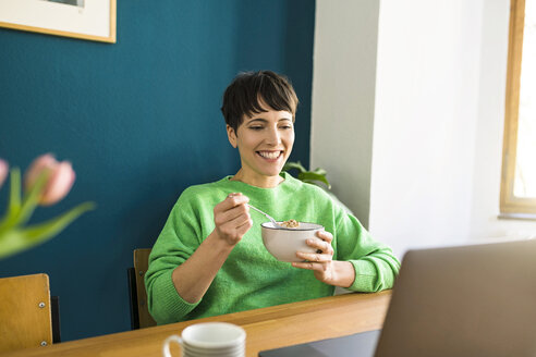 Happy short-haired woman with green pullover working with laptop in home office eating cornflakes in a bowl - SBOF01742