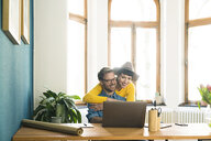 Casual entrepreneur couple in home office working at laptop and hugging each other - SBOF01751
