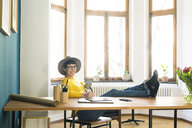 Portrait of happy relaxed businesswoman in home office - SBOF01754