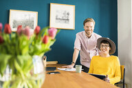 Portrait of happy couple at wooden table in their home office holding tablet - SBOF01757