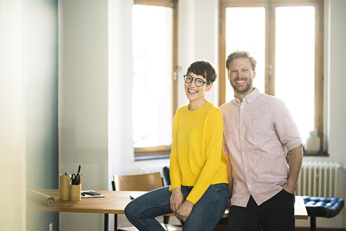 Portrait of happy couple at table in stylish apartment - SBOF01763