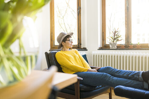 Pensive woman relaxing in lounge chair in stylish apartment looking out of window - SBOF01766
