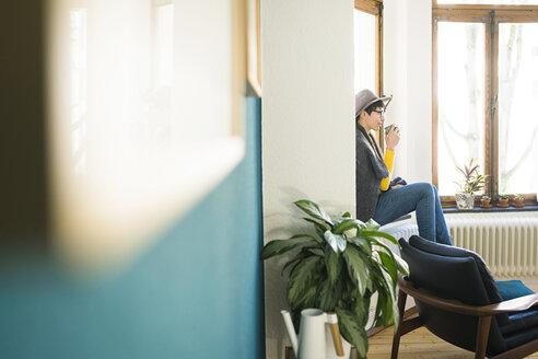 Woman sitting on windowsill in stylish apartment holding coffee mug - SBOF01772