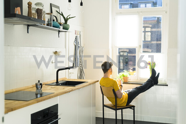 Man relaxing on chair with his feet on the windowsill in his kitchen looking outside - SBOF01778 - Steve Brookland/Westend61