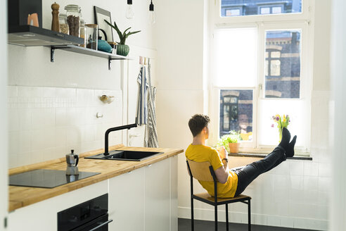 man relaxing on chair with his feet on the window bench in his kitchen looking outside - SBOF01778