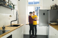 Happy couple with tablet in front of their fridge doing online shopping for groceries - SBOF01781
