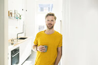 Confident casual man with coffee mug leaning against door case - SBOF01784
