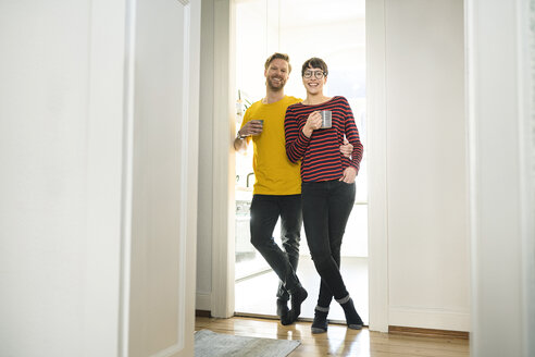 Happy couple leaning in door case in front of their kitchen - SBOF01787