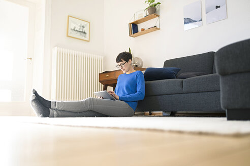 Casual short-haired woman relaxing in modern living room using a tablet - SBOF01793