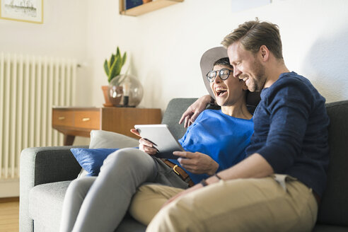 Happy casual couple relaxing on couch using tablet and laughing - SBOF01796