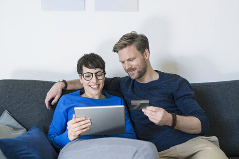 Happy casual couple relaxing on couch using tablet and holding credit card - SBOF01799
