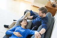Casual couple relaxing on lounge couch in their modern living room - SBOF01802
