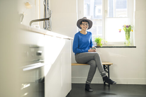 Portrait of smiling sitting on bench in kitchen at the window - SBOF01805