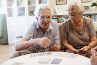 Senior couple playing cards at table in nursing home - MASF11131