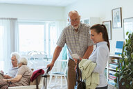 Young woman showing mobile phone to senior man at nursing home - MASF11134