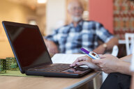 Cropped image of elderly care nurse buying medicine online using laptop and credit card at nursing home - MASF11143