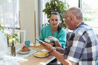 Young nurse and senior man using digital tablet at breakfast table in nursing home - MASF11146